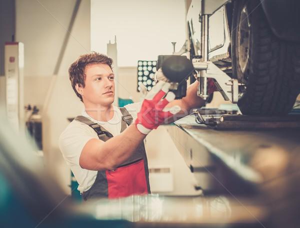 Serviceman checking wheel alignment  in a car workshop  Stock photo © Nejron