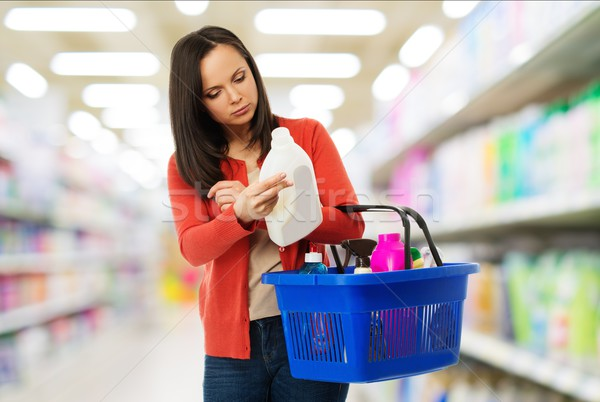 Beautiful brunette woman with basket reading label on cleanser in a shop Stock photo © Nejron