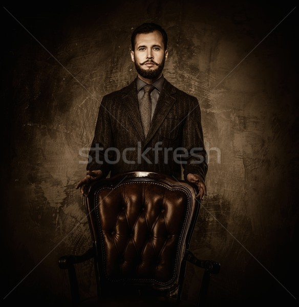 Handsome well-dressed  standing near leather chair  Stock photo © Nejron