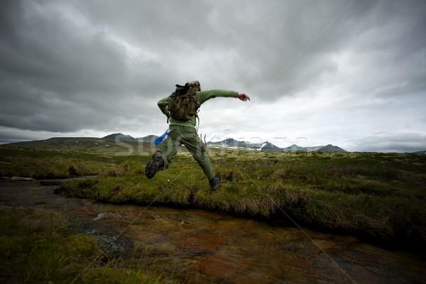 Man hiker jumping across small river Stock photo © Nejron