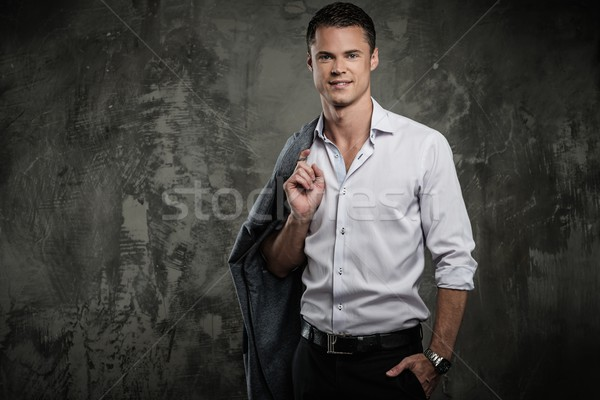 Handsome man in shirt against grunge wall holding jacket over shoulder  Stock photo © Nejron