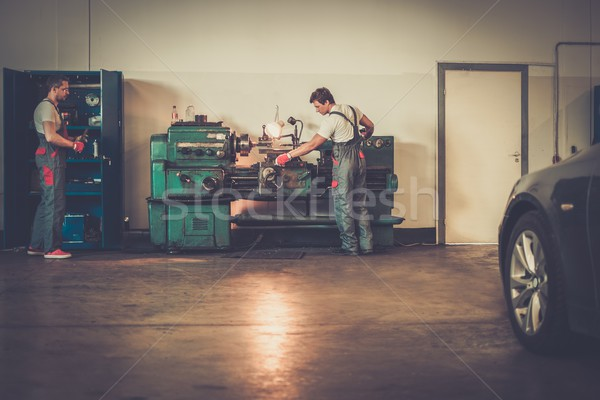 Stock photo: Serviceman working on turning lathe in car workshop