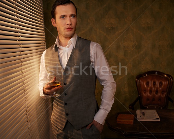 Retro man with a glass standing near window. Stock photo © Nejron