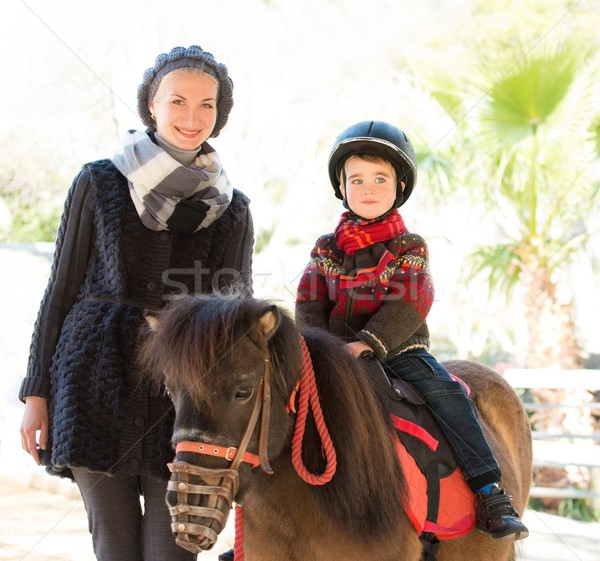 Mother riding her son on a pony wearing protective helmet Stock photo © Nejron