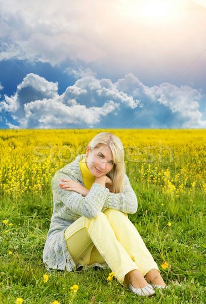 Belle jeune femme séance champ de fleurs ciel fleurs Photo stock © Nejron