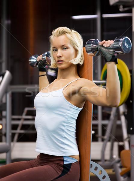 Strong beautiful woman lifting heavy dumbbells Stock photo © Nejron