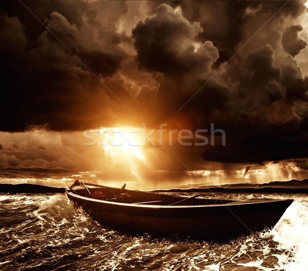 Wooden boat in a stormy sea  Stock photo © Nejron