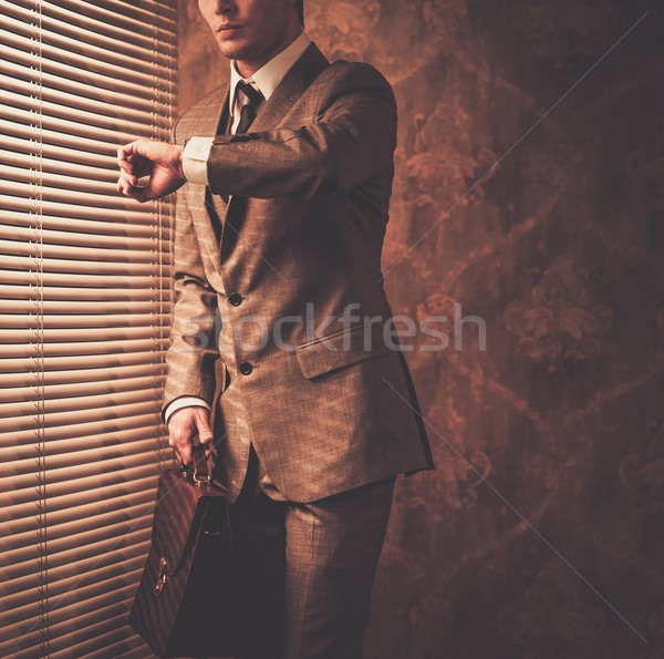 Well-dressed businessman looking at his watch Stock photo © Nejron