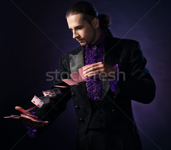 Stock photo: Young brunette magician in stage costume showing card tricks