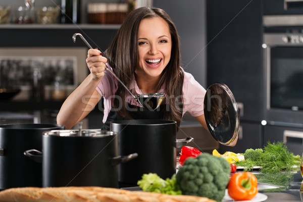 Cheerful young woman in apron on modern kitchen will ladle tasting from pot Stock photo © Nejron