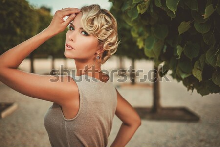 Beautiful blond girl drinks champagne near the river at sunset t Stock photo © Nejron