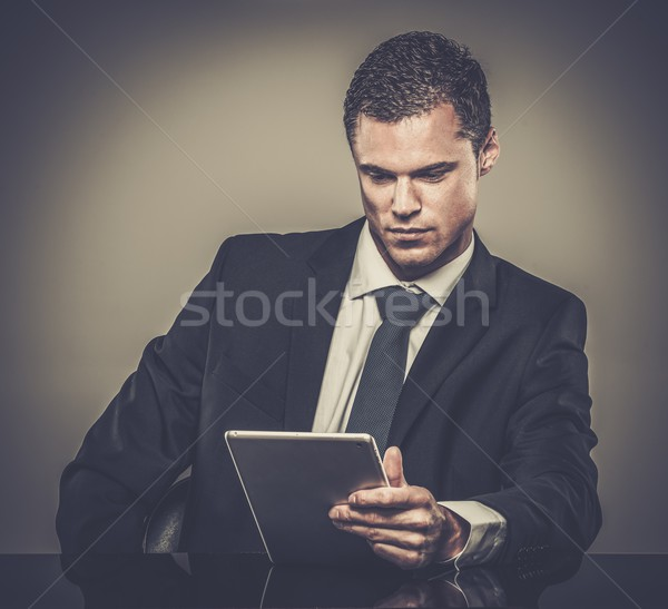 Well-dressed man in black suit with tablet pc Stock photo © Nejron