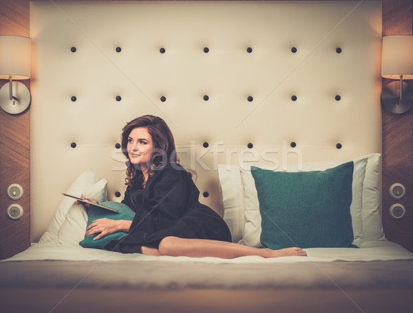 Woman in bathrobe lying on a bed with tablet pc Stock photo © Nejron