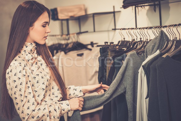 Young woman choosing clothes on a rack in a showroom  Stock photo © Nejron
