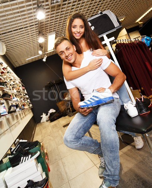 Young beautiful couple choosing sports footwear in a sport outlet Stock photo © Nejron