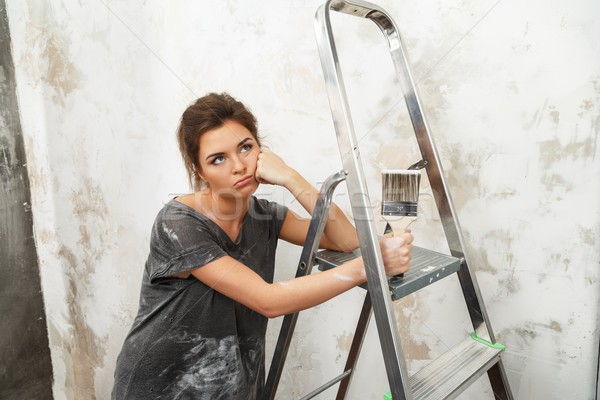 Disgruntled young brunette woman with ladder and painting brush Stock photo © Nejron