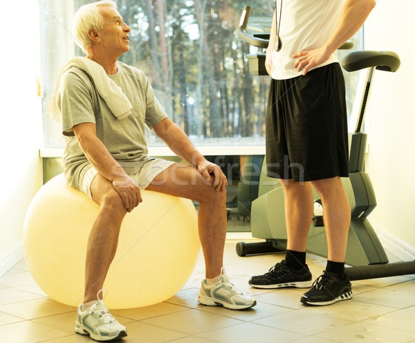 Personal trainer explains to a senior man how to do exercise on a fitness ball Stock photo © Nejron
