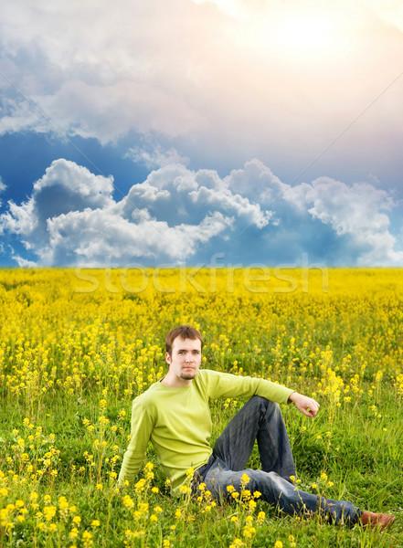 Jeune homme séance champ de fleurs ciel printemps Photo stock © Nejron