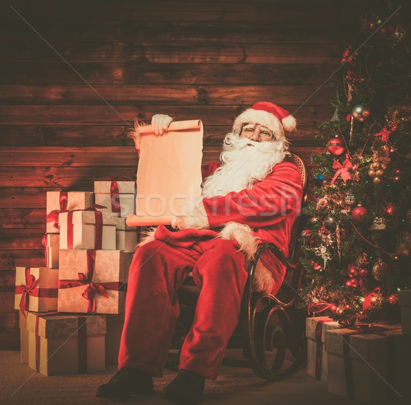 Santa Claus in wooden home interior holding blank wish list scroll Stock photo © Nejron