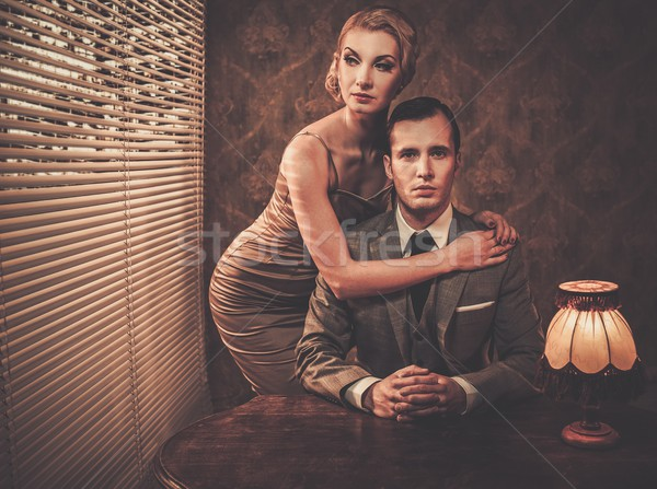 Well-dressed retro couple behind table Stock photo © Nejron
