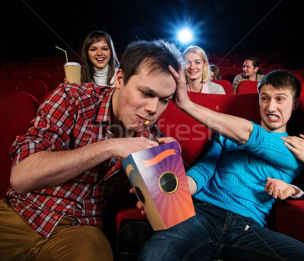 Impudent young man steal popcorn in cinema while people watching movie Stock photo © Nejron