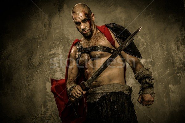 Wounded gladiator with sword covered in blood Stock photo © Nejron