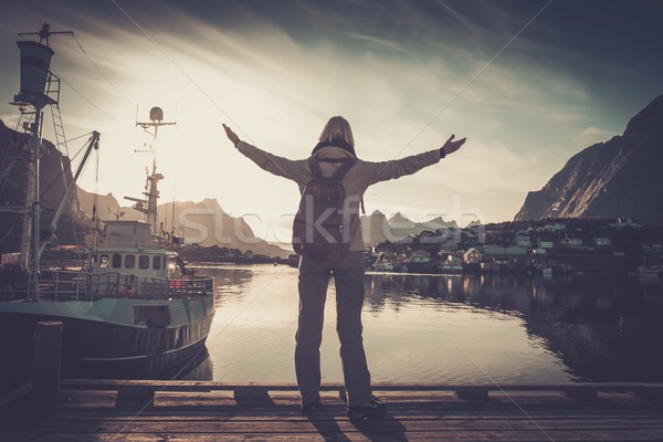Woman traveler looking at sunset in Reine village with arms wide open Stock photo © Nejron
