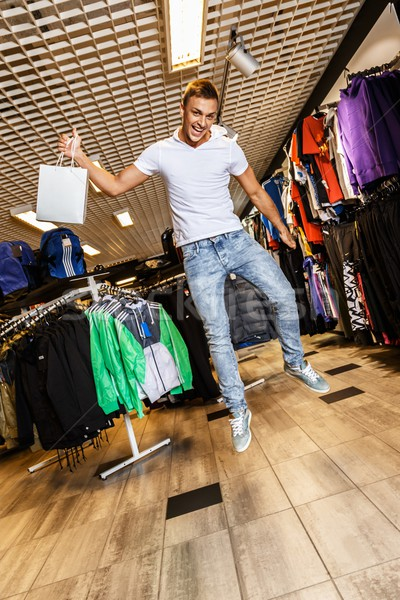 Handsome young man with shopping bag jumping in sport outlet Stock photo © Nejron