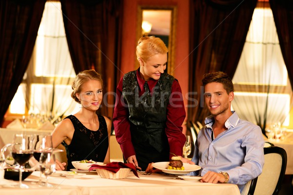 Beautiful young couple in restaurant and waitress bringing meal Stock photo © Nejron