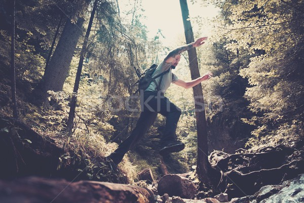Man hiker jumping across stream in mountain forest Stock photo © Nejron