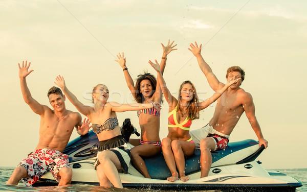 Group of happy multi ethnic friends sitting on a jet ski Stock photo © Nejron