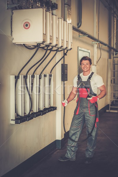 Cheerful serviceman holding hose with unbottled motor oil in a car workshop Stock photo © Nejron