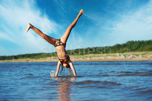 young girl making cartwheel in the water Stock photo © Nejron