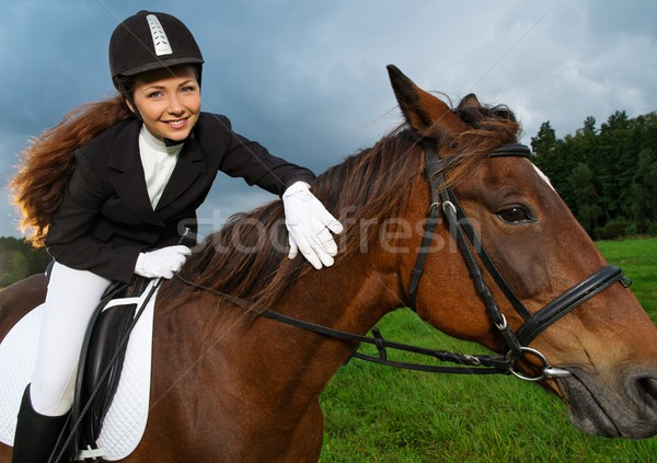 Beautiful smiling girl sitting on a horse outdoors  Stock photo © Nejron