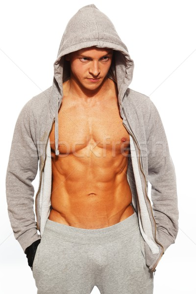 Handsome man in grey hoodie showing his abdominal muscles Stock photo © Nejron