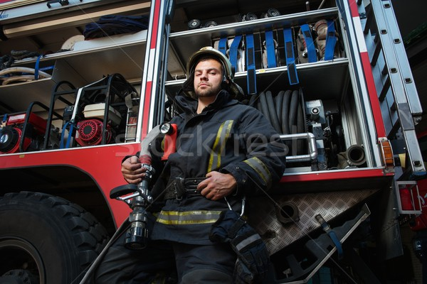 Firefighter near truck with equipment with water water hose over shoulder  Stock photo © Nejron