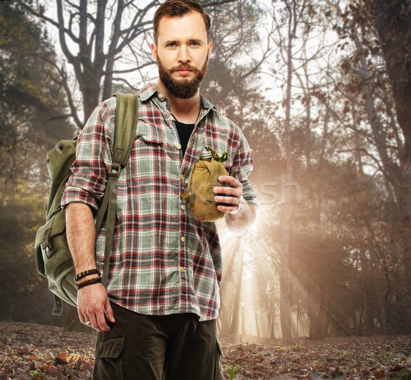 Handsome traveler with backpack and flask in autumnal forest  Stock photo © Nejron