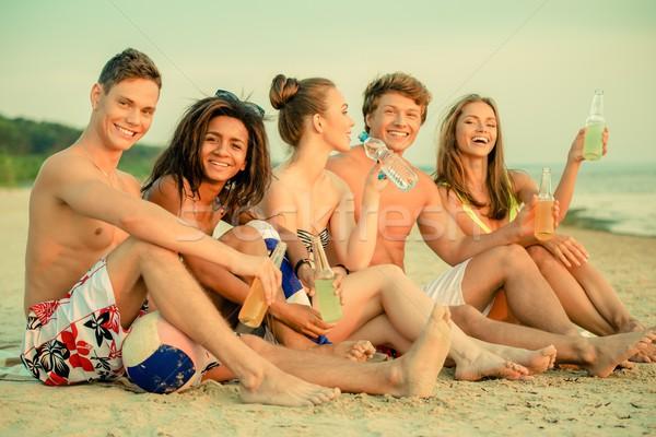 Csoport többnemzetiségű barátok italok ül tengerpart Stock fotó © Nejron
