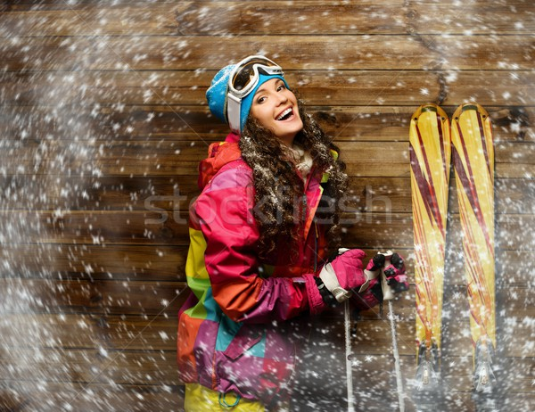 Smiling woman with skies standing against wooden house wall  in a snow Stock photo © Nejron