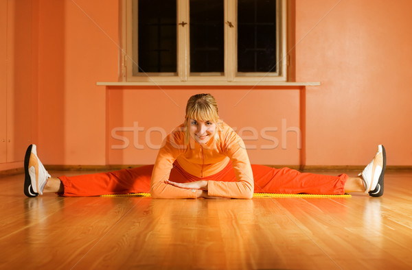 Beautiful fitness trainer does splits on a floor Stock photo © Nejron