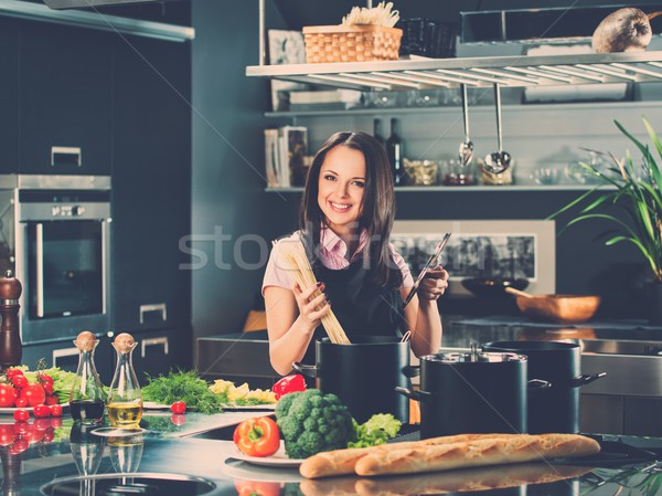 Smiling young woman cooking spaghetti on a modern kitchen  Stock photo © Nejron