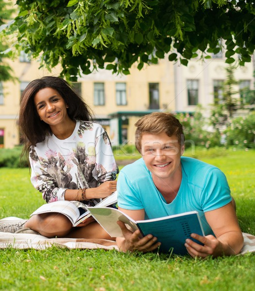 Multi ethnic students couple preparing for final exams in a city park  Stock photo © Nejron