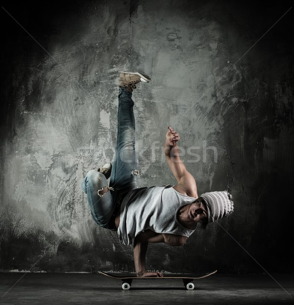 Young b-boy man doing brake dancing movements on skateboard Stock photo © Nejron