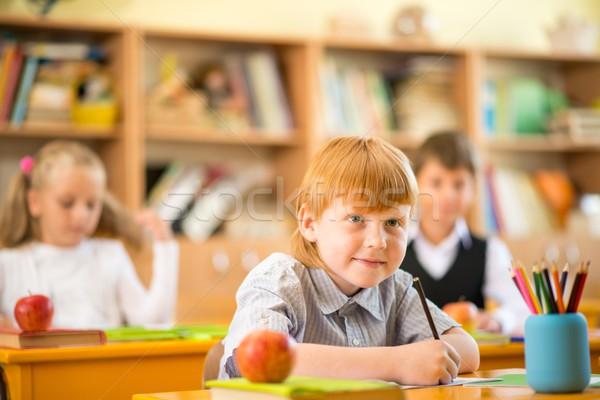 Little redhead schoolboy behind school desk during lesson  Stock photo © Nejron