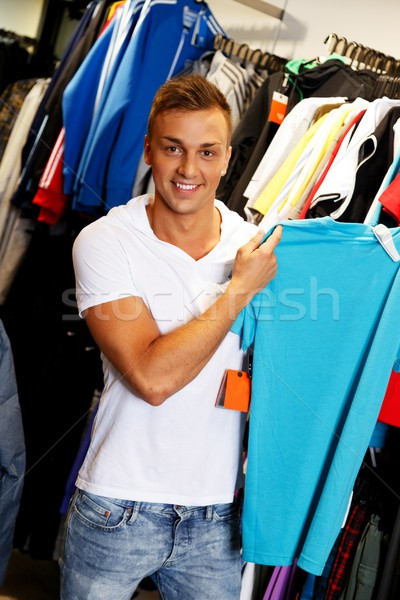 Handsome young man choosing t-shirt in a sport outlet Stock photo © Nejron