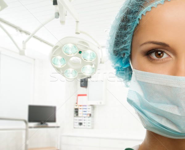 Young woman doctor in cap and face mask in surgery room interior Stock photo © Nejron