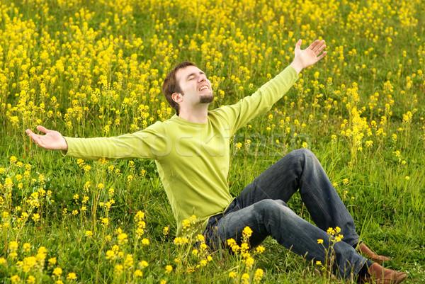 Heureux jeune homme séance champ de fleurs printemps herbe Photo stock © Nejron