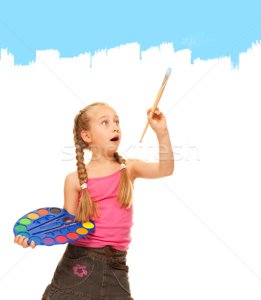 Beautiful little girl painting with blue paint