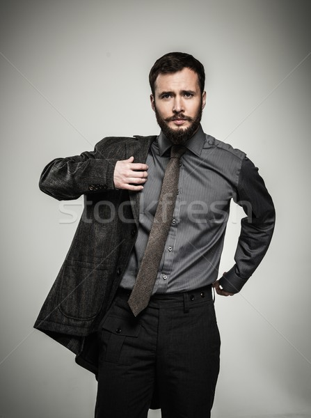 Handsome man with beard putting on jacket  Stock photo © Nejron