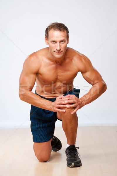 Handsome muscular man doing fitness exercise. Stock photo © Nejron